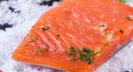 Piece of salted salmon, served with dill and spices on sea salt over black wooden table. Square image with selective focus