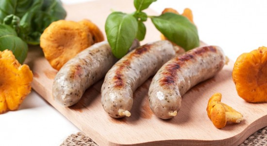 Grilled sausages with chanterelle and basil, server on wooden cutting board with sacking cloth over white